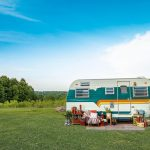 An image of a cute white, green, and yellow caravan parked in a field.